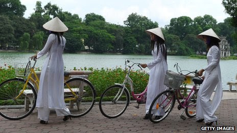 Women in traditional ao dai dress and conical hats