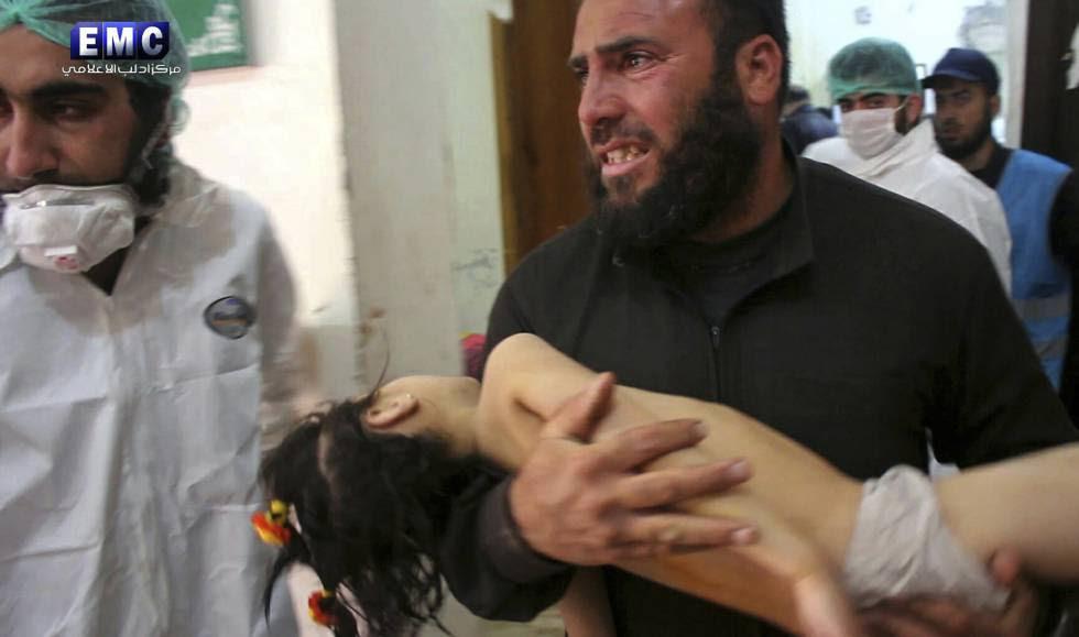 Homem leva menina nos braços ao pronto-socorro na localidade atacada com armas químicas.