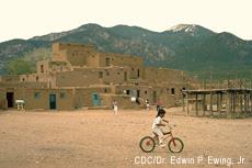 Photograh of a Native American boy riding a bicycle at Taos Pueblo, Taos, New Mexico