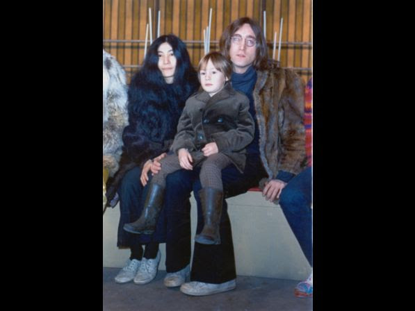 Beatle John Lennon poses with his son Julian, sitting on his lap, and his companion Yoko Ono at an unknown location in 1968.