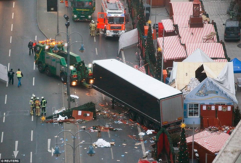 Carnage: O camião usado para matar uma dúzia de pessoas em Berlim na noite passada foi rebocado para longe da cena como um requerente de asilo de 23 anos de idade estava sendo interrogado