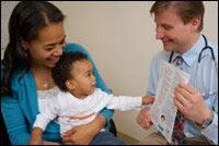 Madre con su bebé en brazos en una consulta con el pediatra