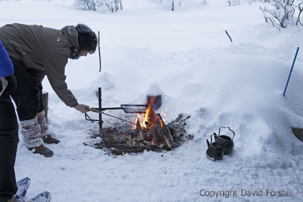 06D-1241 Person Cooking Sausages on an Open Camp Fire Outside of the Kahvikeidas Laavu in Winter Yllas Lapland Finland