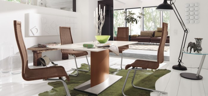 This dining rooms severity is balanced simply by adding the fun green cowhide rug and warm brown of the dining chairs.