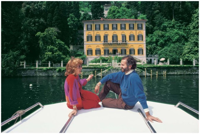 Fashion designer Gianni Versace, along with Lalla Spagnol, on a boat in front of his seventeenth-century Villa Fontanelle