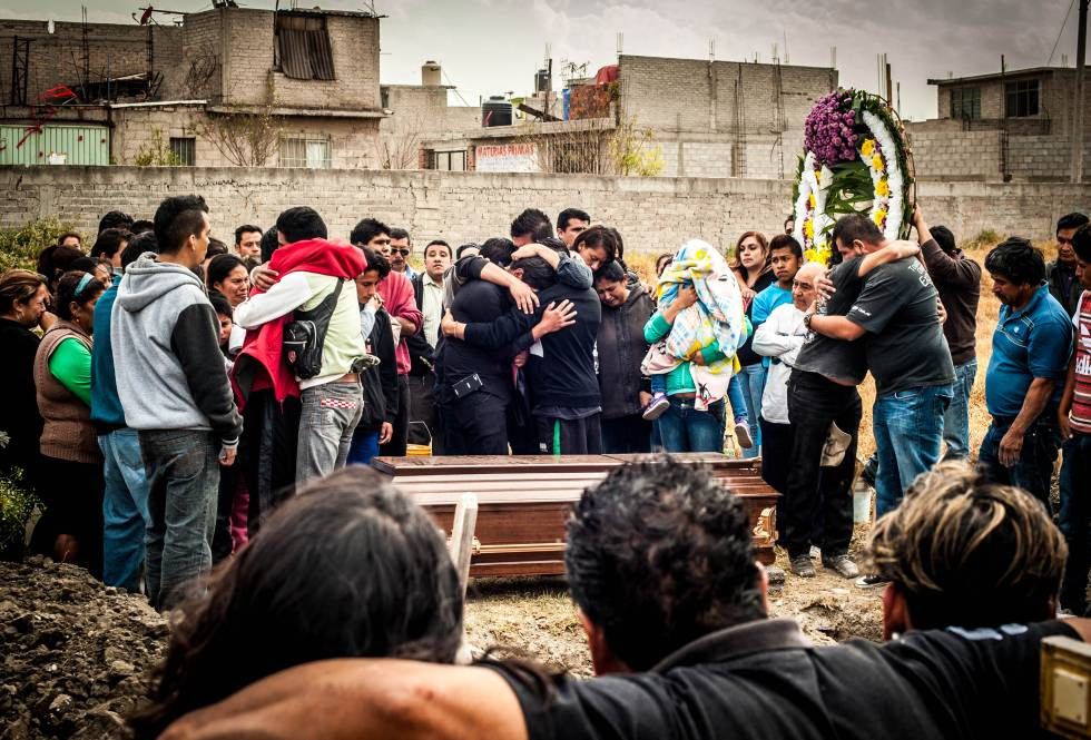 Familiares, amigos y vecinos de Carolina lloran y se abrazan al rededor del féretro.