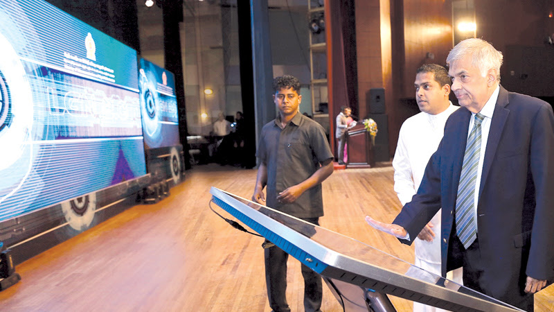 Prime Minister Ranil Wickremesinghe launching the upgraded Lanka Government Network 2.0, which is to network 860 government institutes with digital facilities. Telecommunication and Digital Infrastructure Minister Harin Fernando looks on. Picture by Rukmal Gamage
