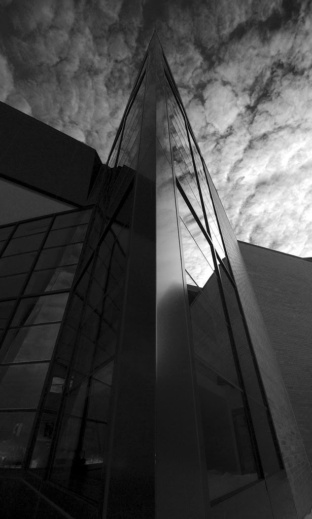 A black and white photo of the pointed corner of a building, with many windows, and a dramatic sky reflected in the windows.