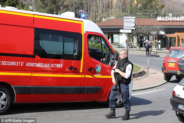 A policeman wearing a bulletproof vest stands near a firefighters vehicle on a road near the Tocqueville high school in the southern French town of Grasse