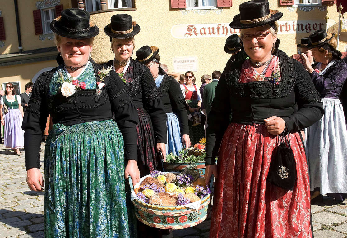 Women in typical clothes carry basket full with food during a traditional annual harvest festival procession in Lofer, Austrian province of Salzburg, Sunday, Otc. 2, 2011. AP Photo /Kerstin Joensson)