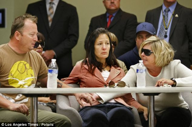 Michael McStay holds hands with his mother Susan Blake at a table with McStay's wife Erin in the middle during a press conference