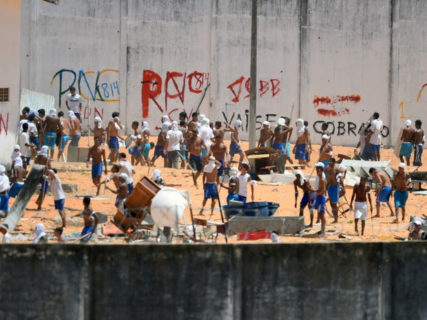 Presos são vistos durante um confronto de facções na penitenciária de Alcaçuz, perto de Natal, no Rio Grande do Norte (Foto: Andressa Anholete/AFP)
