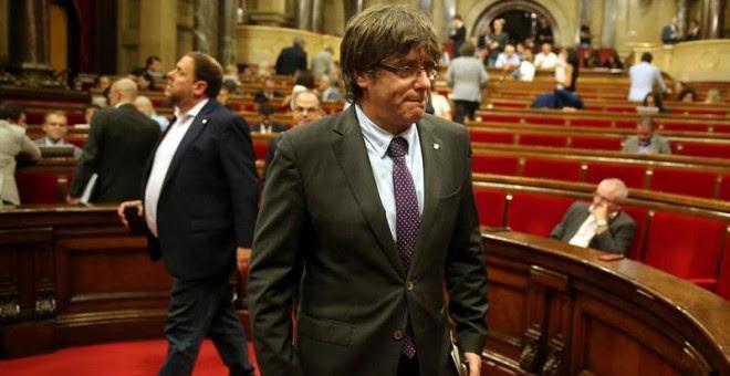 El presidente de la Generalitat, Carles Puigdemont (d) y el vicepresidente del Govern, Oriol Junqueras (i), abandonan hoy el hemiciclo del Parlament de Catalunya. EFE/Toni Albir