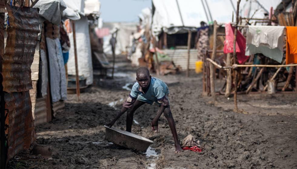 Un niño sostiene un barreño en una de las calles embarradas del campo de desplazados de Malakal, Sudán del Sur.