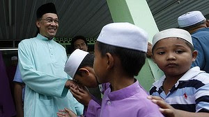 Pucker up … young boys kiss the hand of Anwar in his Penang electorate.