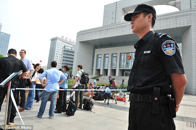 A police officer stands guard outside Hefei Intermediate People's Court today. TV cameras were set up outside awaiting the sentencing of Gu Kailai