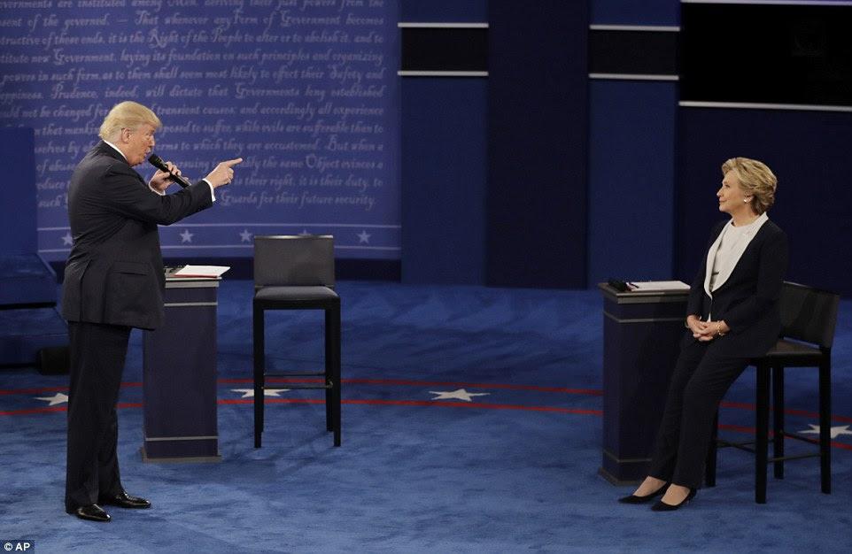 Donald Trump se levanta e aponta o dedo para Hillary Clinton como ele fala durante o segundo debate presidencial no domingo