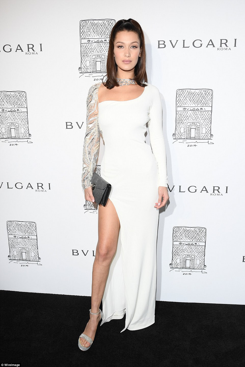 Stunning:Bella's bare back wasn't the only thing on full display as she showed off her model legs in the dress which featured a thigh-high split and asymmetric sleeves