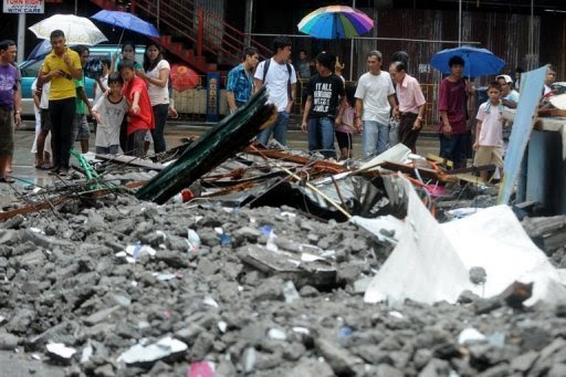 People look at debris after a wall collapsed as super-typhoon Nanmadol moved throughQuezon City, east of Manila