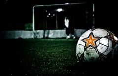Imagen de una pelota de fútbol en primer plano y al fondo una portería