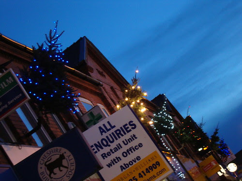 Christmas trees in flag poles in Stockton Heath