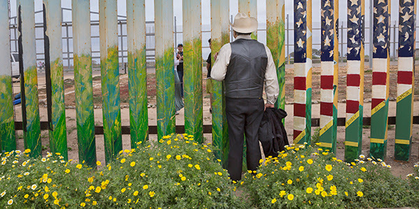 A man standing in front of a border fence with an American flag painted on it