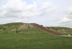 """""""Two walkers scale Monks Mound at Cahokia Mounds Historic Site. Several walkers and runners use the promenade for exercise. The mound is 100 feet tall, and at last count, 154 steps. """"  Image & Caption Courtesy of the St. Louis Post-Dispatch."""