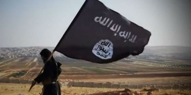 An ISIS insurgent seen walking with the terror group's flag.