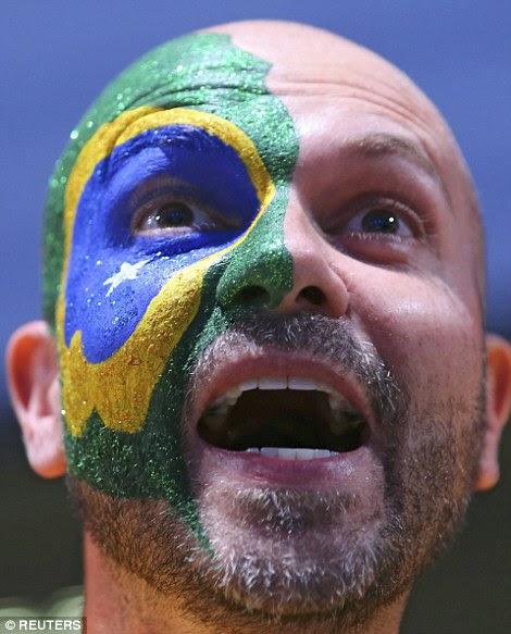 Um ventilador Brasil pinta sua bandeira em seu rosto