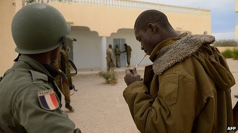 Malian soldier with French insignia watches soldiers enter house in Timbuktu. 28 Jan 2013