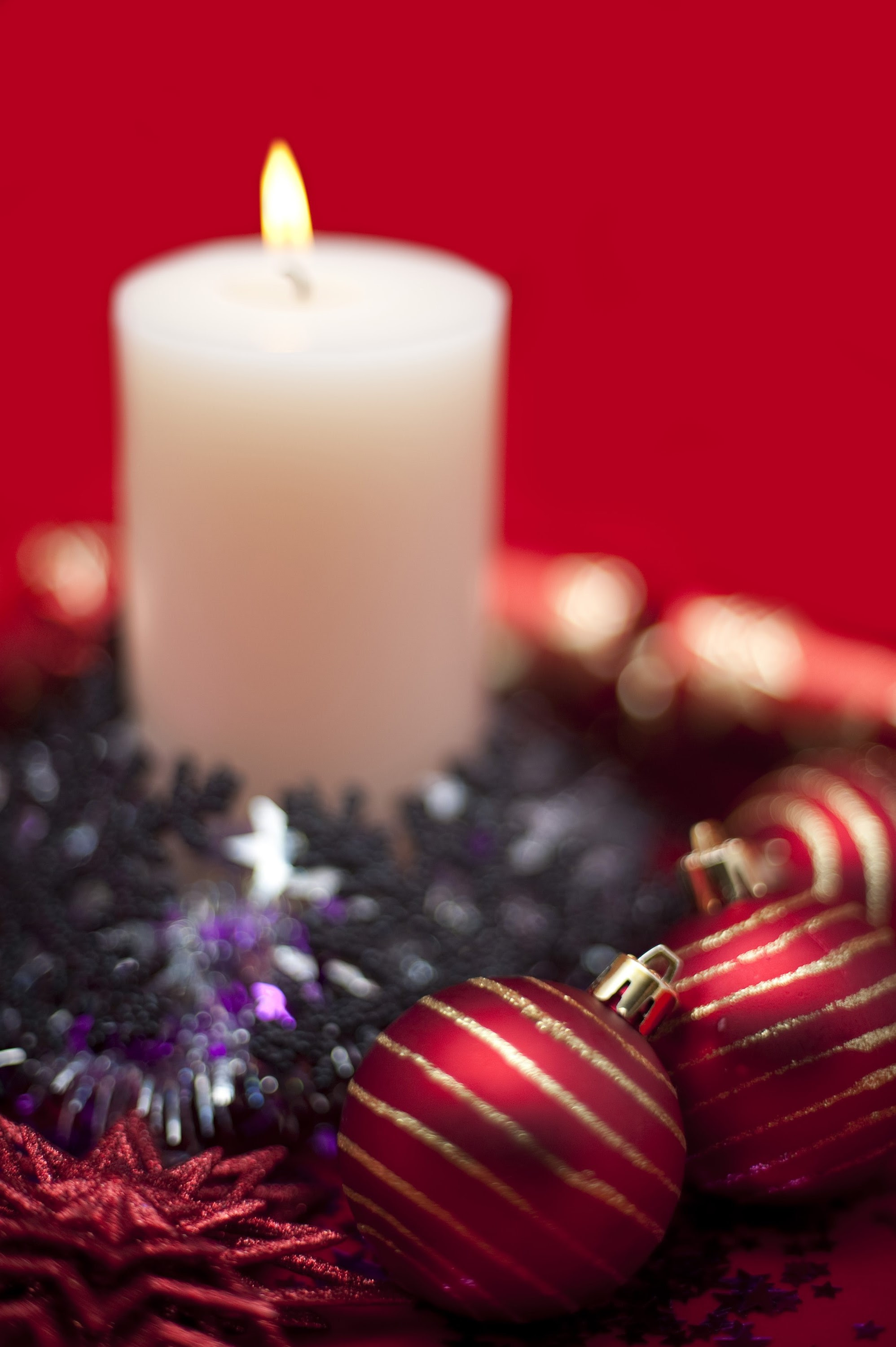 lit christmas candle and various sparkling christmas decoration