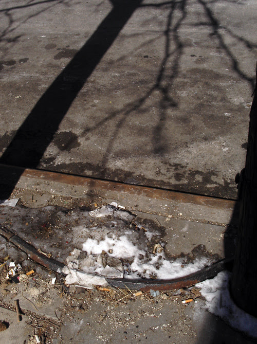 last remains of snow, with shadows and cigarette butts