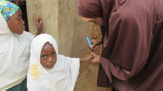 La pequeña Haguagua Abubacar, de 3 años, acaba de ser inmunizada en Dambatta y Muria Shehu le marca el dedo con un rotulador para evitar una doble vacunación.