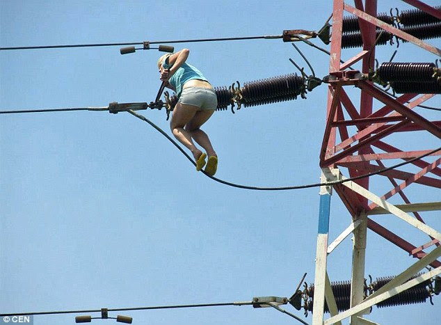 Death-defying: The drug-addled climber balances precariously on the wire, which she managed to mount in a pair of flimsy sandals