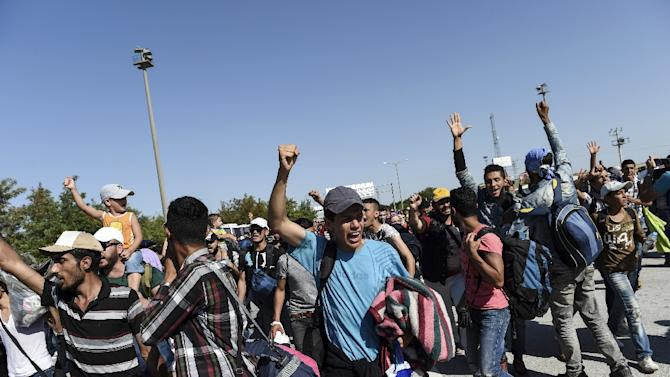 Syrian migrants and refugees chant as they march along the highway towards the Turkish-Greek border at Edirne on September 18, 2015