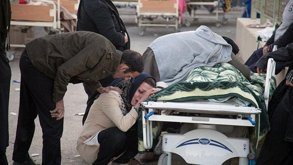 A woman reacts next to a dead body following an earthquake in Sarpol-e Zahab in Kermanshah, Iran. The 7.3-magnitude quake was centered 31 kms outside the eastern Iraqi city of Halabja yesterday, according to measurements from the US Geological Survey. Its impact was felt as far we   st as the Mediterranean coast with worst damage appearing to be in Iran's western Kermanshah province, which sits in the Zagros Mountains dividing Iran and Iraq. (Tasnim News Agency / Handout via REUTERS )