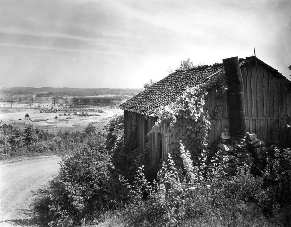 Early Construction K-25 plant with one of original houses Oak Ridge Tennessee 1942