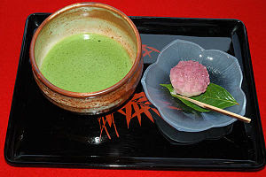 English: A tray with a prepared bowl of matcha...