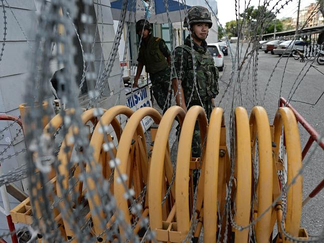 Military coup ... Thai soldiers stand guard at a roadblock outside the Defence Ministry b