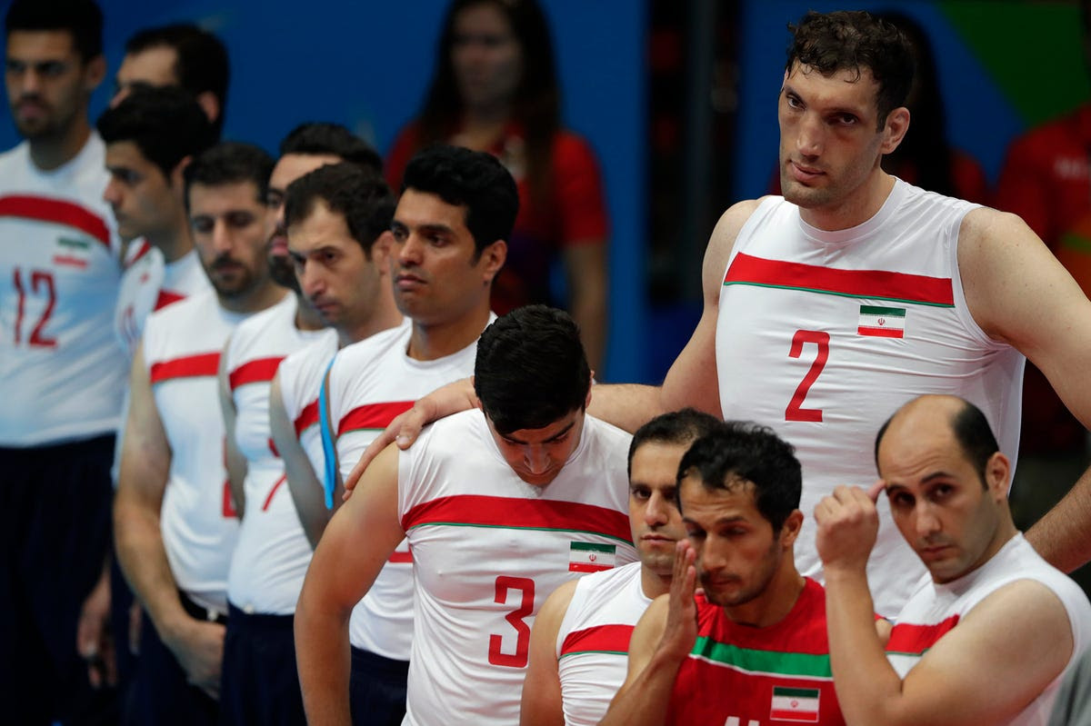 Members of Team Iran's sitting volleyball team observe a moment of silence for Iranian cyclist Sarafraz Bahman Golbarnezhad who died of a heart attack following a crash at the Rio Paralympics.