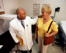 Photograph of a male doctor talking with a senior female patient
