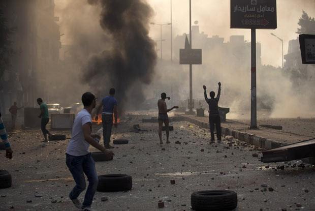 Manifestantes pró e contra a Irmandade Muçulmana se enfrentam neste domingo (6) nas ruas do Cairo (Foto: AFP)