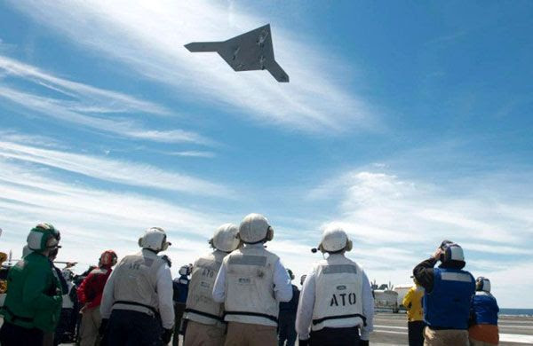 Crew members watch as the X-47B UCAV soars over the flight deck of the USS George H.W. Bush, on May 14, 2013.