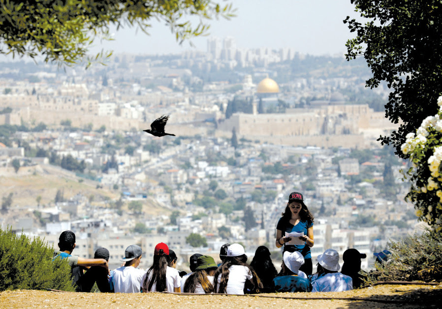 A CROW fies past as schoolchildren gather at a look-out point on the Armon Hanatziv Promenade in Jer