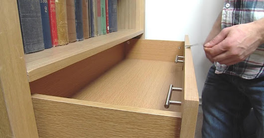 The man removes the handles from the drawer and attaches them to the inside. The reason? Amazing!