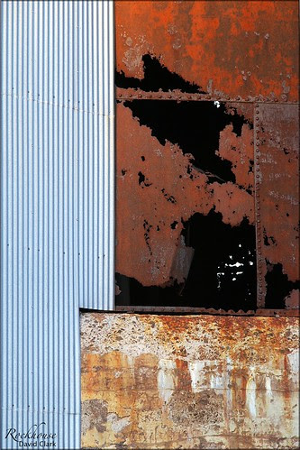 An abstract composition of shapes and textures -- mostly blocks, including lines in corrugated steel, red rusted metal, and decaying cement.