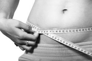 Mujer midiéndose la cintura con una cinta métrica