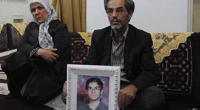 El taxista Aziz, junto a su esposa, sostiene la imagen de su hijo Majid.  Kaveh Kazemi