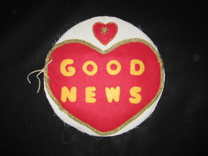 "Fabric heart pillow with words ""Good News"" on it"