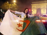 An Algeria soccer team fan celebrates with her national flag on the Champs Elysees in Paris after their team defeated  Burkina Faso in their 2014 World Cup qualifying second leg playoff soccer match